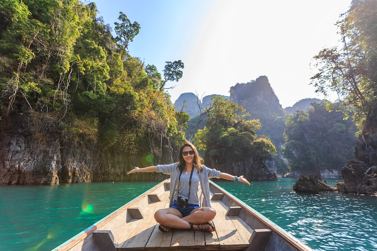 photo-of-woman-sitting-on-boat-spreading-her-arms